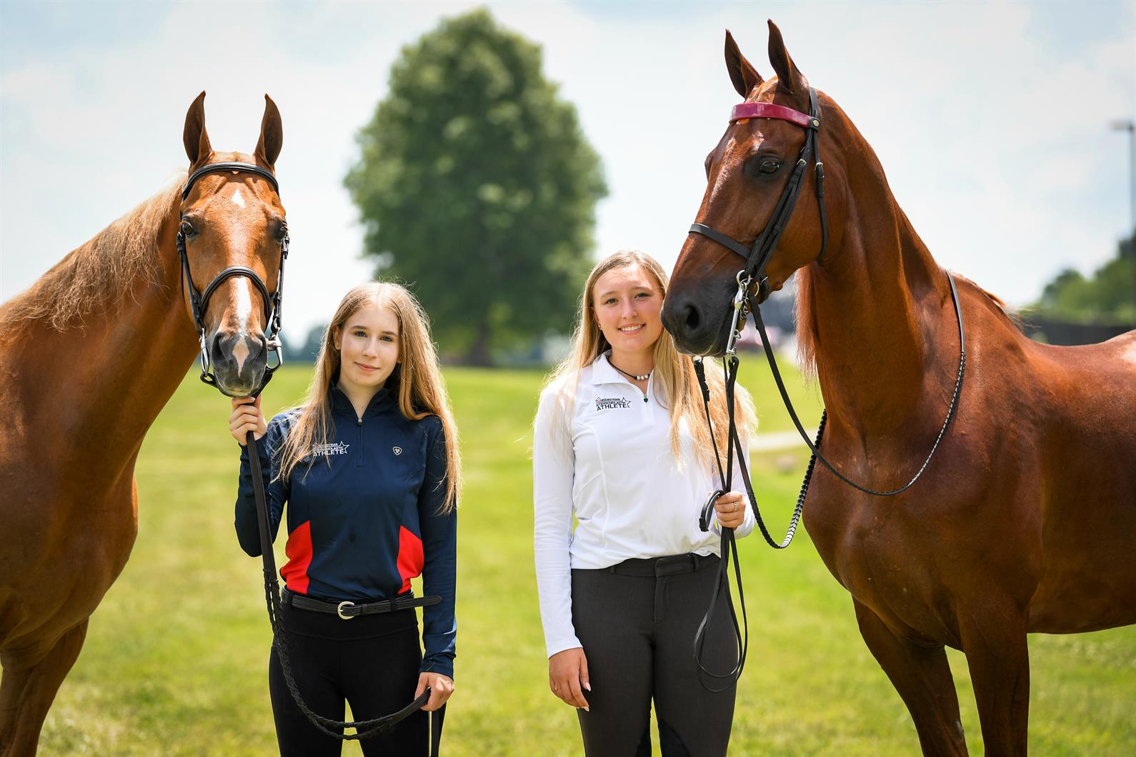 Two interscholastic equestrians posing with Saddlebred horses